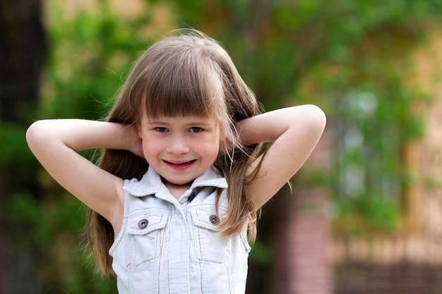 Porträt eines hübschen kleinen langhaarigen blonden vorschulkindmädchens im ärmellosen weißen kleid mit den händen hinter ihrem kopf, die gegen unscharfen hintergrund im freien lächeln. unschuldiges glückliches kindheitskonzept.