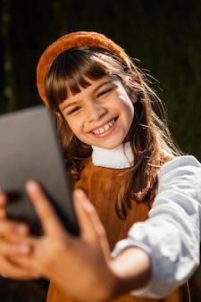 Porträt eines hübschen kleinen mädchens, das ein selfie nimmt