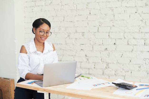 Porträt eines hübschen lächelnden afroamerikanischen büroangestellten, der an einem schreibtisch mit einem computer sitzt
