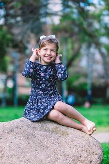 Porträt eines hübschen lächelnden kleinen kindermädchens, das im park draußen steht