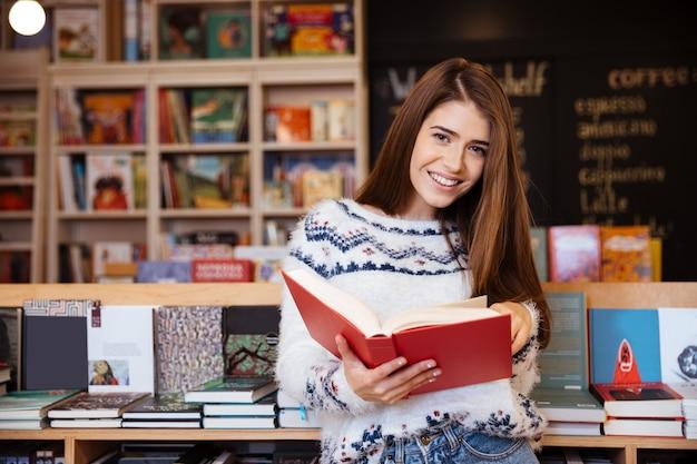 Porträt eines hübschen lächelnden mädchens, das drinnen in der bibliothek ein buch liest und in die kamera schaut