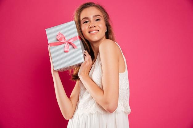 Porträt eines hübschen lächelnden mädchens, das geschenkbox hält