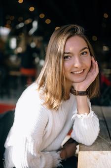 Porträt eines hübschen lächelnden mädchens mit unscharfem caféhintergrund