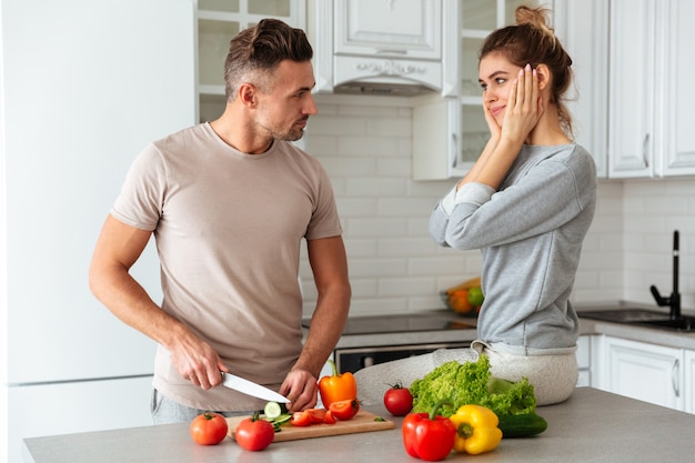 Porträt eines hübschen liebevollen paares, das zusammen salat kocht
