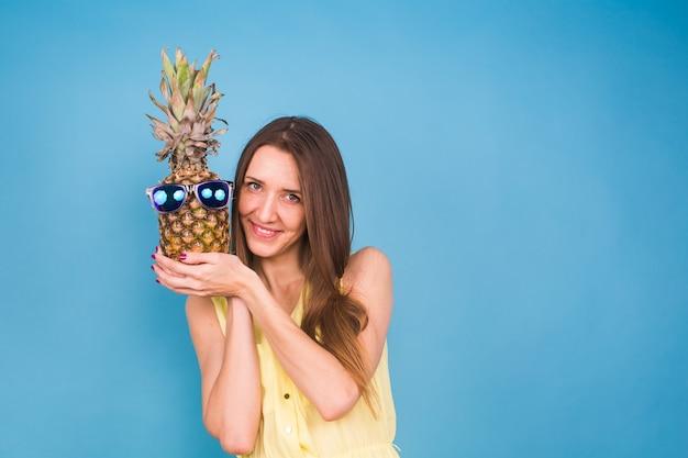 Porträt eines hübschen lustigen sommermädchens, das ananas in der sonnenbrille lokalisiert über blauem hintergrund hält.