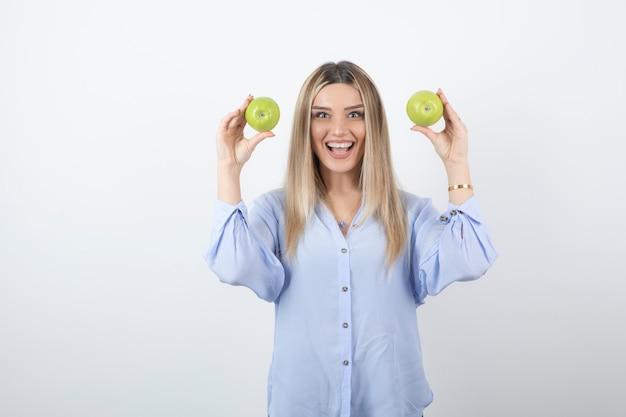 Porträt eines hübschen mädchenmodells, das frische äpfel steht und hält.
