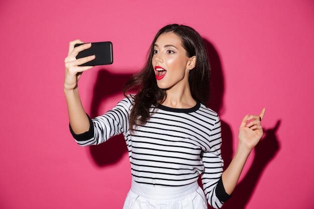 Porträt eines hübschen mädchens, das ein selfie nimmt