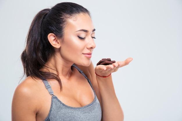 Porträt eines hübschen mädchens, das schokolade riecht, lokalisiert auf einer weißen wand
