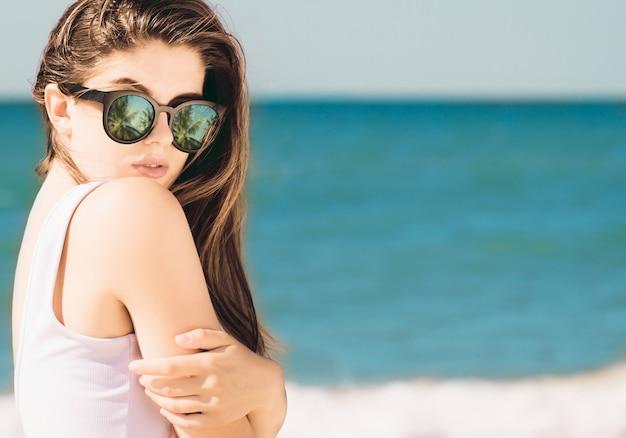 Porträt eines hübschen mädchens mit dem langen haar in der modischen sonnenbrille mit der palmenreflexion, die auf dem strand aufwirft