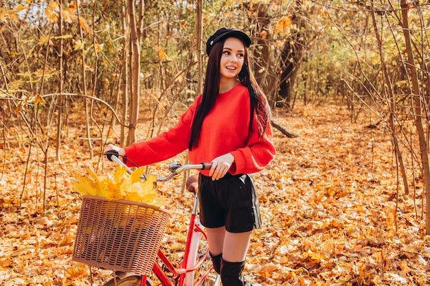 Porträt eines hübschen mädchens mit einem roten fahrrad im herbstwald