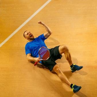 Porträt eines hübschen männlichen tennisspielers, der seinen erfolg auf einer hofwand feiert. menschliche emotionen, sieger, sport, siegeskonzept