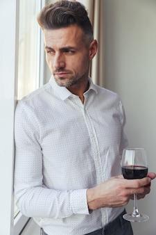Porträt eines hübschen nachdenklichen mannes kleidete im hemd an