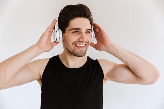 Porträt eines hübschen optimistischen lächelnden sportmannes lokalisiert über hörender musik der weißen wand mit kopfhörern.