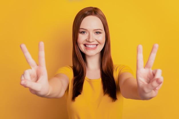 Porträt eines hübschen positiven mädchens, das v-zeichen friedenssymbol einzeln auf gelbem hintergrund gestikuliert