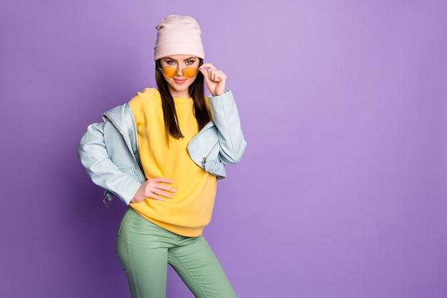 Porträt eines hübschen, prächtigen jugendmädchens, das ihre spezifikationen berührt, sieht am herbstwochenende gut aus und trägt lässige kleidung einzeln auf violettem farbhintergrund