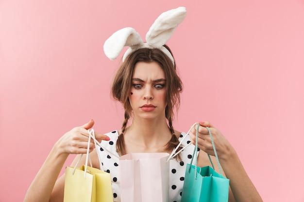 Porträt eines hübschen reizenden mädchens, das hasenohren trägt, die isoliert stehen und einkaufstaschen tragen