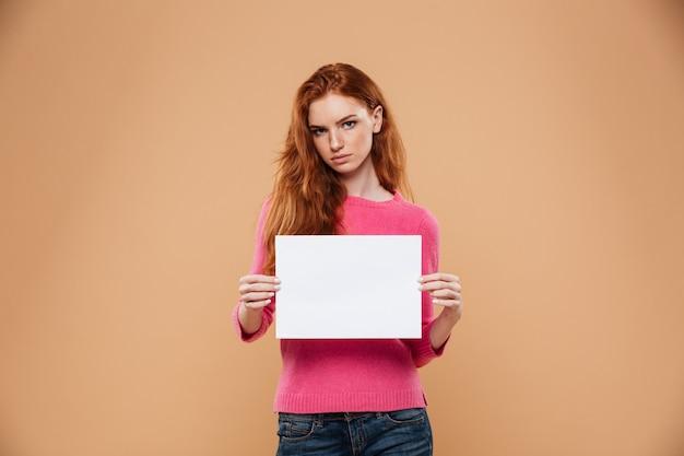 Porträt eines hübschen rothaarigemädchens des umkippens, das leeres weißes plakat zeigt