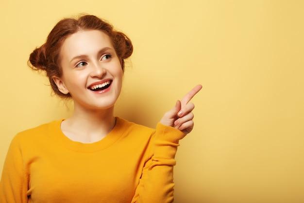 Porträt eines hübschen rothaarigen mädchens, das finger weg über gelbem hintergrund zeigt