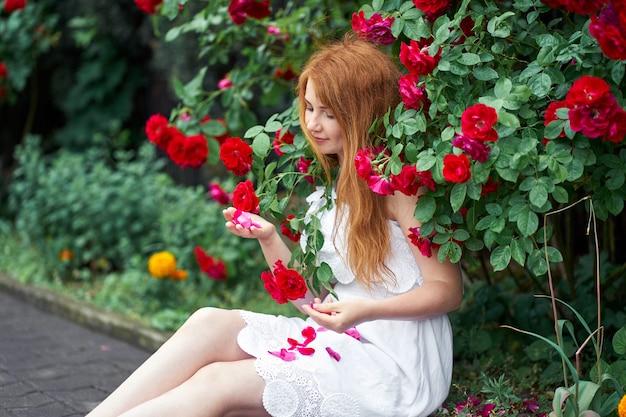 Porträt eines hübschen rothaarigen mädchens gekleidet in einem weißen hellen kleid auf einem hintergrund der blühenden rosen.