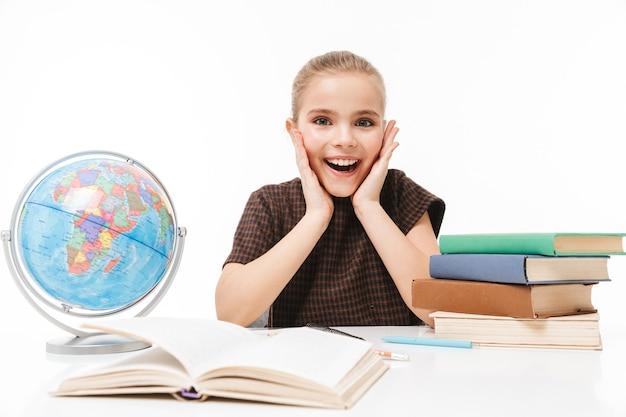 Porträt eines hübschen schulmädchens, das bücher liest und hausaufgaben macht, während es am schreibtisch in der klasse sitzt, isoliert über weißer wand