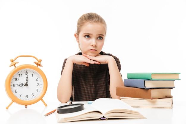 Porträt eines hübschen schulmädchens mit großem wecker auf dem schreibtisch, das bücher in der klasse studiert und liest, isoliert über weißer wand