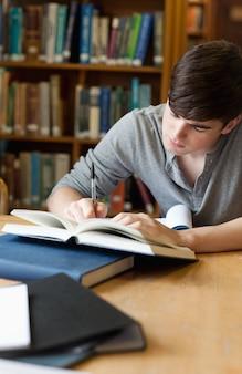 Porträt eines hübschen studenten, der einen aufsatz schreibt