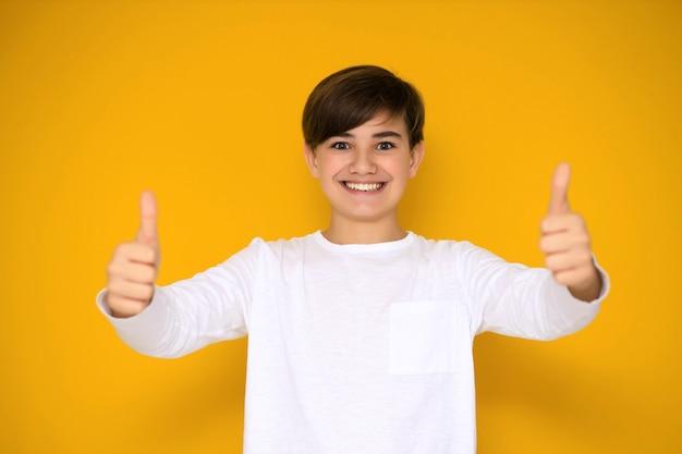 Porträt eines hübschen teenagers 12-13 jahre alt auf gelbem grund.