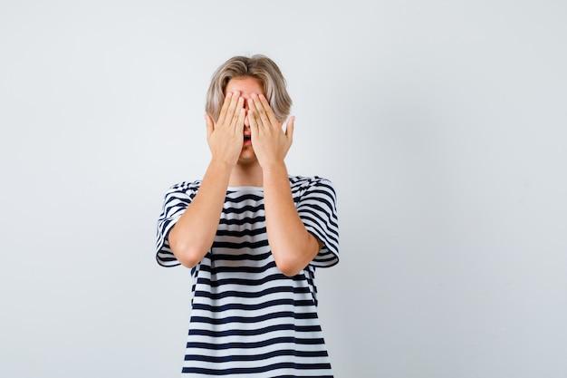 Porträt eines hübschen teenagers, der das gesicht mit den händen im gestreiften t-shirt bedeckt und verängstigte vorderansicht schaut
