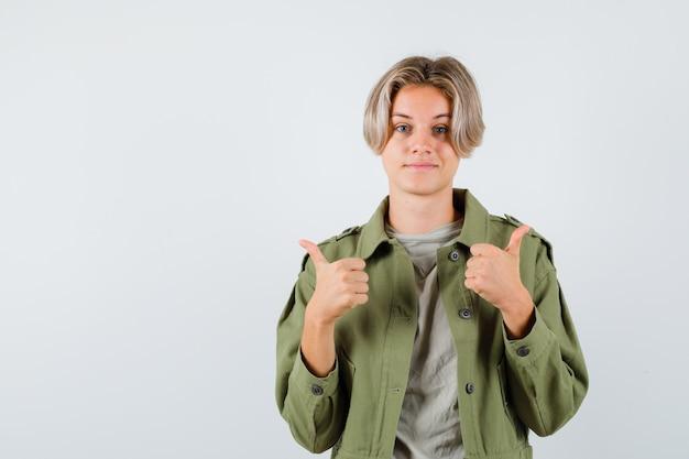 Porträt eines hübschen teenagers, der doppelte daumen in grüner jacke zeigt und erfreute vorderansicht schaut