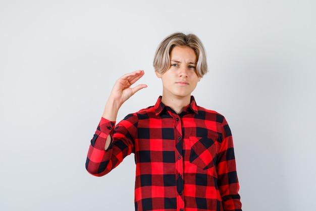 Porträt eines hübschen teenagers, der eine bla-bla-bla-geste in kariertem hemd zeigt und sarkastisch aussieht