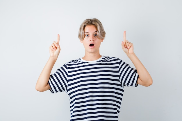 Porträt eines hübschen teenagers, der in gestreiftem t-shirt nach oben zeigt und schockierte vorderansicht schaut