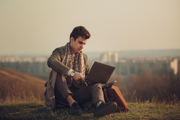 Porträt eines hübschen und erfolgreichen jungen geschäftsmannes, der auf dem gras, gegen das schattenbild der stadt im abstand sitzt. stilvolles bild eines mannes in einem modernen mantel.