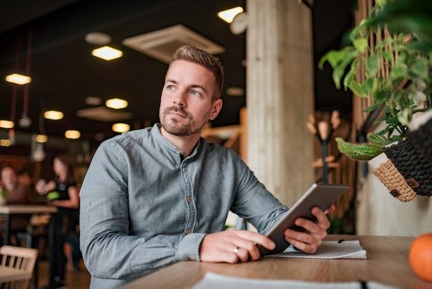 Porträt eines hübschen zufälligen geschäftsmannes mit digitaler tablette im café.