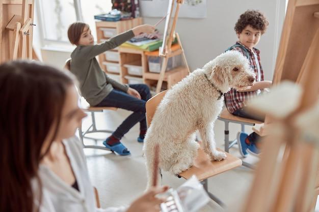 Porträt eines hundeschülers auf einer gruppenzeichnungsstunde in einem modernen hellen klassenzimmer