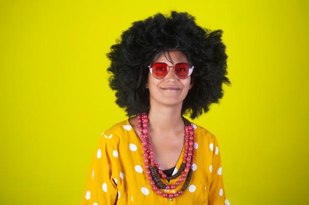 Porträt eines indischen lächelnden mädchens mit afro-lockiger frisur und herzförmigen brillen auf gelber wand