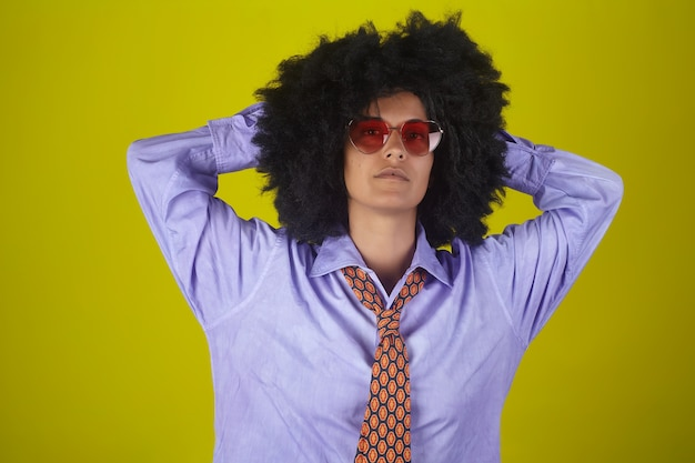 Porträt eines indischen mädchens in der brille und im herrenhemd und in der krawatte mit afro-lockiger frisur auf gelber wand