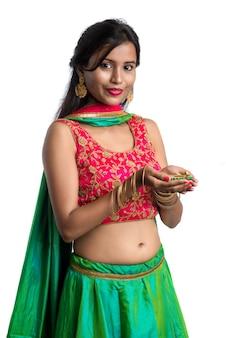 Porträt eines indischen traditionellen mädchens, das diya hält und diwali oder deepavali feiert