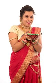 Porträt eines indischen traditionellen mädchens, das pooja thali mit diya während des festes des lichts auf weißem hintergrund hält. diwali oder deepavali