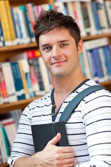 Porträt eines intelligenten studenten, der ein buch steht in der bibliothek hält