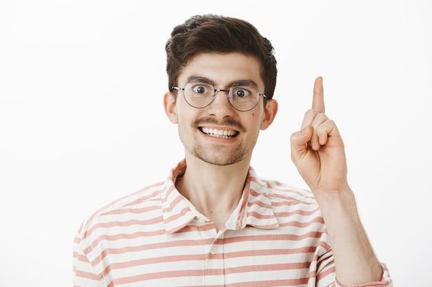 Porträt eines intensiven ernsthaften europäischen männlichen lehrers in runden gläsern, zeigefinger in eureka hebend oder während des nachhilfeunterrichts, erklären der hausaufgaben, überwältigt und aufgeregt mit liebevoller arbeit über graue wand