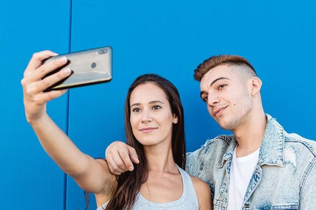 Porträt eines isolierten jungen und glücklichen paares, das ein selfie mit einem smartphone in blau nimmt