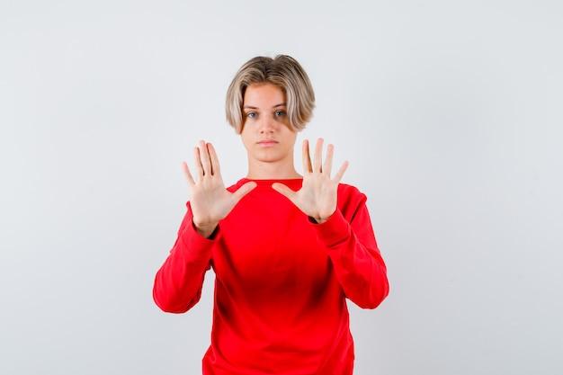 Porträt eines jugendlich blonden mannes, der eine stopp-geste im roten pullover zeigt und selbstbewusste vorderansicht sieht