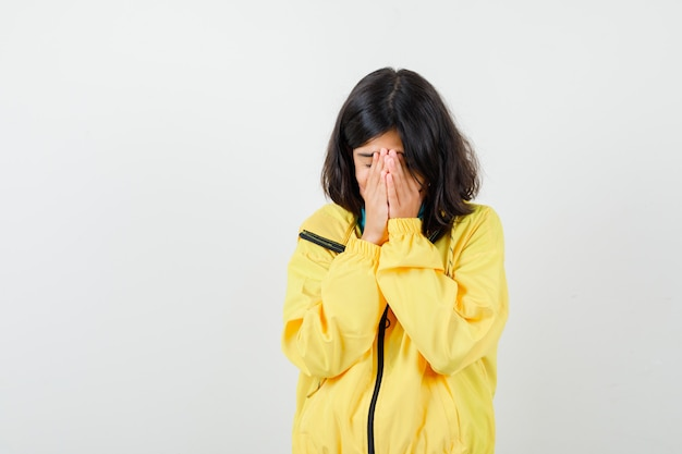Porträt eines jugendlich mädchens, das die hände im gesicht in der gelben jacke hält und deprimiert vorderansicht schaut