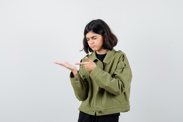 Porträt eines jugendlichen mädchens, das auf ihre handfläche zeigt, die in einer armeegrünen jacke beiseite ausgebreitet ist und eine fokussierte vorderansicht sucht