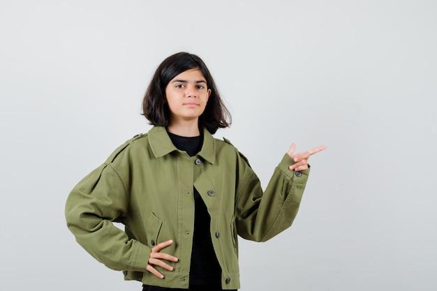 Porträt eines jugendlichen mädchens, das beiseite zeigt, die hand in der armeegrünjacke an der taille hält und stolze vorderansicht schaut