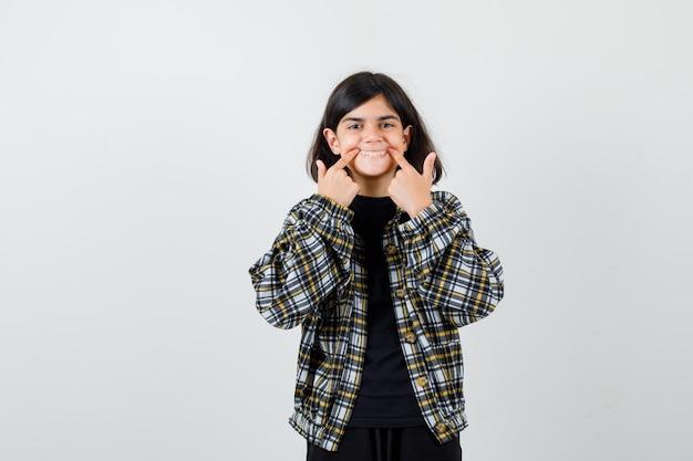 Porträt eines jugendlichen mädchens, das den mund mit den fingern im lässigen hemd öffnet und freudige vorderansicht schaut