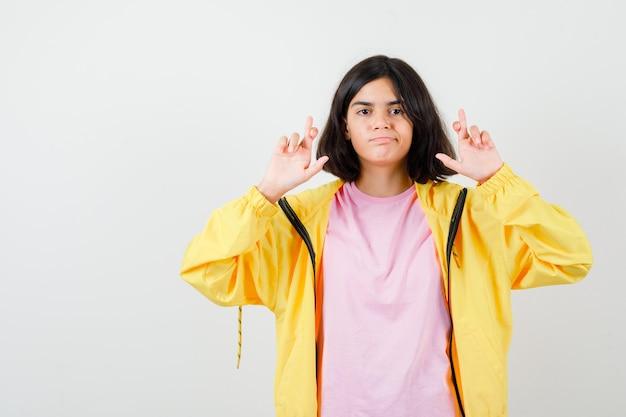 Porträt eines jugendlichen mädchens, das die daumen in t-shirt, jacke und zuversichtlicher vorderansicht hält