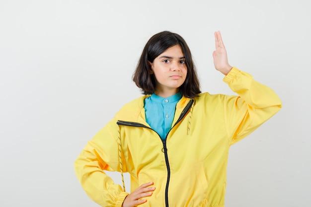 Porträt eines jugendlichen mädchens, das die hand hebt, die hand in der gelben jacke an der taille hält und selbstbewusste vorderansicht schaut
