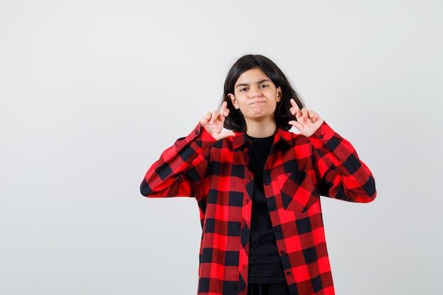 Porträt eines jugendlichen mädchens, das gekreuzte finger in lässigem hemd zeigt und zögerliche vorderansicht schaut