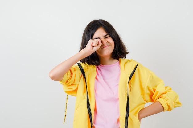 Porträt eines jugendlichen mädchens, das ihr auge in t-shirt, jacke reibt und müde vorderansicht schaut